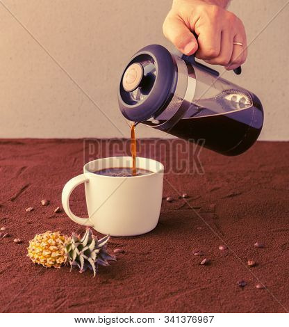 Male Hand Holds French Press And Pours Coffee Into A Cup