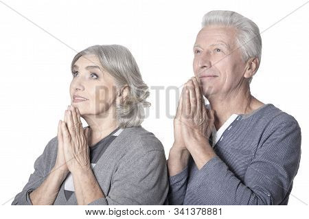 Close Up Portrait Of Happy Senior Couple Praying On White Background