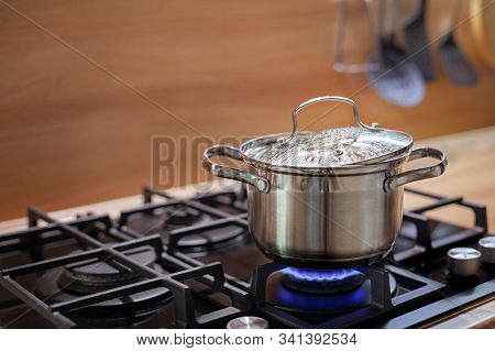 Water Boils In A Pan On A Gas Stove, Steam Comes Out From Under The Lid, The Concept Of Cooking