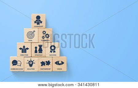 Wooden Block Stacking Pyramid With Icon Leader Business On Blue Background. Key Success Factors For