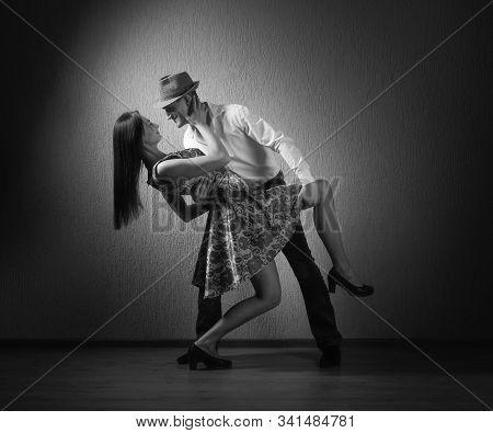 Young Beautiful Woman In Black Dress And Man In White Shirt Dancing Tango.
