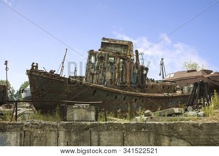 An Old Abandoned Rusty Metal Ship Unfit For Use Lies On A Pier On The River Bank. An Old Unusable Sh