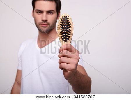 A Confident Young Handsome Guy With Dark Hair In A White T-shirt Shows The Camera A Wooden Comb. The