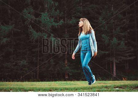 A Young Girl Walks Near A Dense Forest