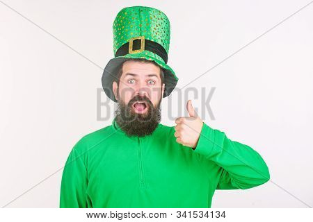 Happy Saint Patricks Day. Hipster In Leprechaun Hat And Costume Keeping Mouth Open. Bearded Man Cele
