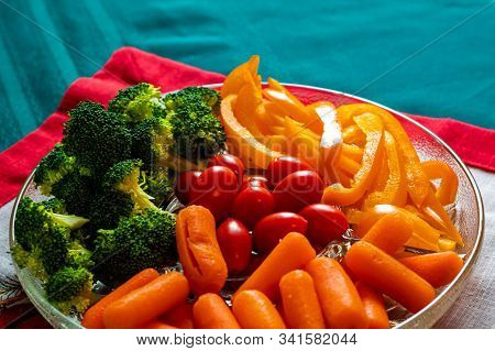 A Glass Dish Of Raw Veggies Consists Of Broccoli Florets, Baby Carrots, Grape Tomatoes And Sliced Ye