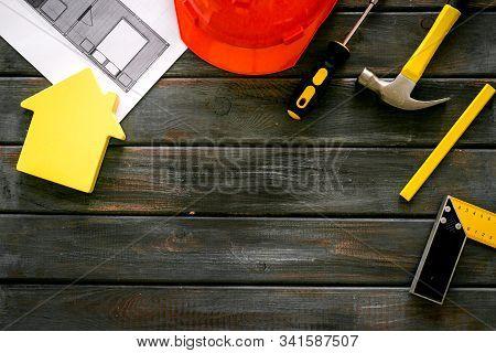 Builder Work Desk With Hard Hat, Instruments And Blueprints On Dark Wooden Background Top-down Frame