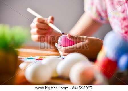 Young Girl Painting Easter Eggs For Eastertime At Home