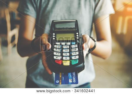 Close Up Of Hand Hold Credit Card Swiping Machine To Pay. Online Payment . Paying By Credit Card