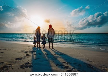 Happy Family With Two Kids Walk On Sunset Beach