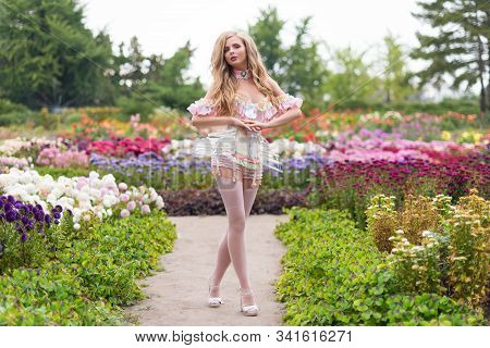 Sexy Blonde Woman Wearing Beautiful Lingerie With Stockings And Corset, Walking In Blooming Garden.