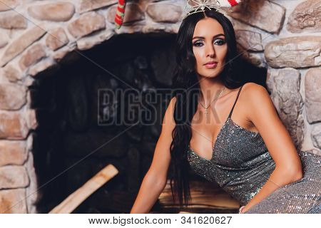 Portrait Of A Beautiful Brunette Girl Boobs. New Year Interior