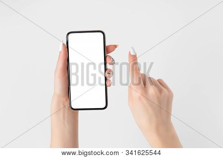 Female Hand Holding And Touching On Mobile Smartphone With White Screen. Isolated On White. Photo Te