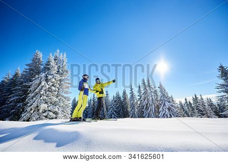 General View Of Happy Family After Skiing On Sunny Day. Man And Woman On Skis In Goggles Stopping On