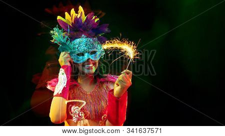 Beautiful Young Woman In Carnival Mask, Stylish Masquerade Costume With Feathers And Sparklers Invit