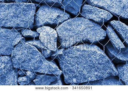 Gabion Wall Closeup. Textured Background Toned In Trendy Classic Blue Color. Gabion Is Stones In Wir
