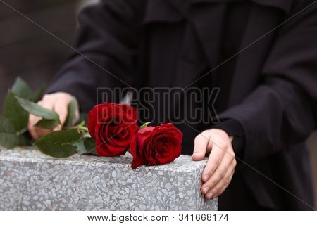 Woman With Red Roses Near Light Grey Tombstone Outdoors, Closeup. Funeral Ceremony