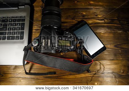 Modern Dslr Camera, Smartphone And Laptop On Rustic Wooden Table. Top View