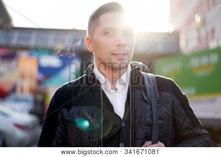 Young man walking in city during day, lensflare effect.