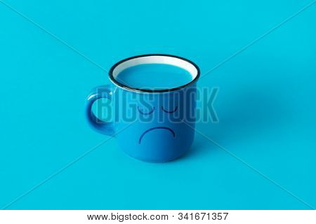 closeup of a blue mug, with a sad face drawn in it, and full of a blue liquid, on a blue background