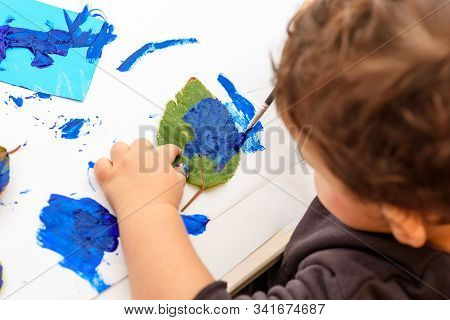 Little Child Painting Leaves Blue Color, Crafts And Art Therapy. Classic Leaf Painting Art. Child Of