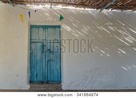 Blue Wooden Door And Straw Roof With Dramatic Light Rays And Shadows At Abadoned Church Ermita De Sa