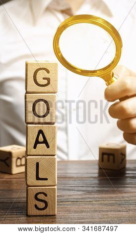 Wooden Blocks With The Word Goals And Businessman. The Concept Of Achieving Business Goal. Reaching