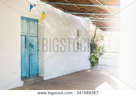 Lightened Blue Wooden Door And Straw Roof With Dramatic Light Rays And Shadows At Abadoned Church Er