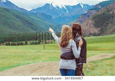 The Couple Stands Against The Background Of Mountains Show Their Hands In The Distance
