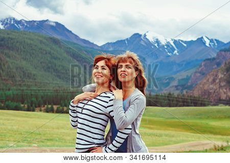 Two Girls Stand In An Embrace On The Background Of Beautiful Mountains