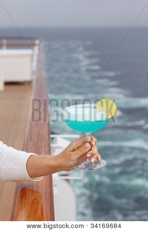 Woman hand holds blue cocktail in glass at background of cruise liner deck