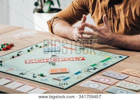 Kyiv, Ukraine - November 15, 2019: Cropped View Of Man Sitting At Table With Monopoly Game