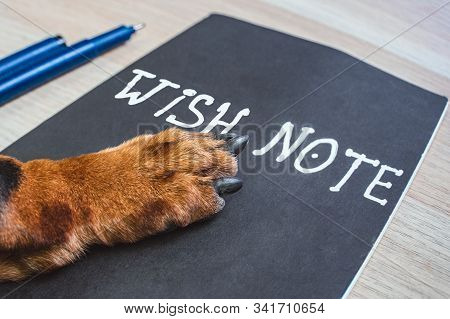 Ginger Dog Paw On Wish Note At The Table. Wish List Or New Year Resolution Concept.