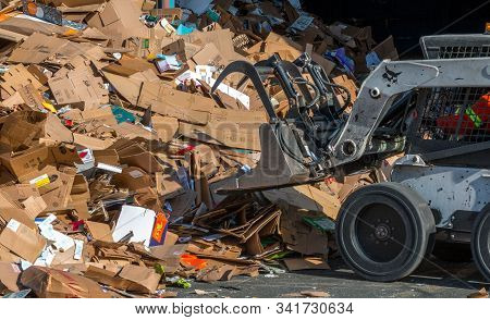 Victoria, British Columbia / Canada- 30/04/2019: A Bobcat Operator Piles Waste Cardboard For Process
