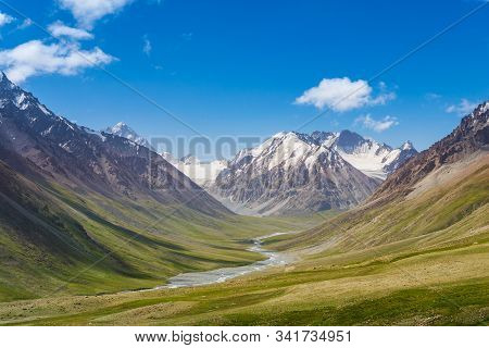 Majestic Snow Capped Mountains Or Glacier Landscape With Green Alpine Meadows And Stream Running In