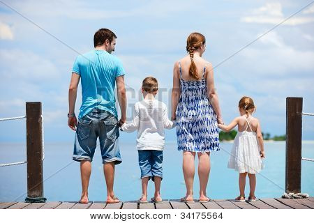 Family on wooden dock enjoying ocean view