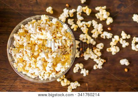 Top View Of Popcorn In A Glass Cup With Popcorn Pread On A Wooden Table.