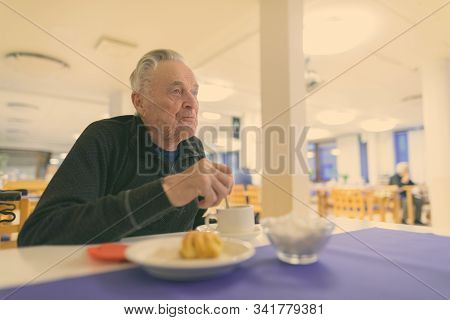 Senior Man Eating At The Cafeteria In Nursing Home