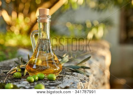 olive oil with fresh olives and leaves
