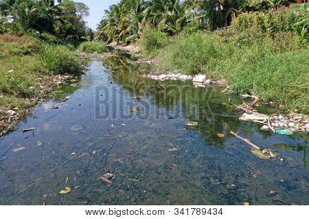 Water pollution. Raw sewage and plastic trash dumped in stream in poor slum village