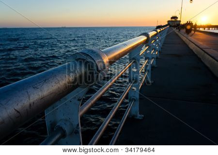 Sun setting in the background with the pier in the foreground poster