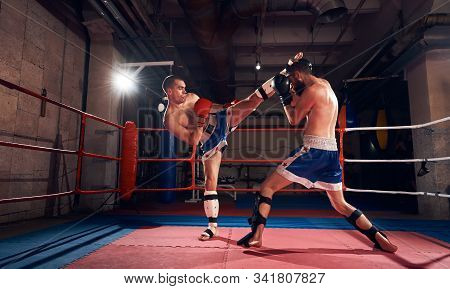 Two Athletic Sportsmen Kickboxers Practicing Kickboxing In The Ring At The Sport Club