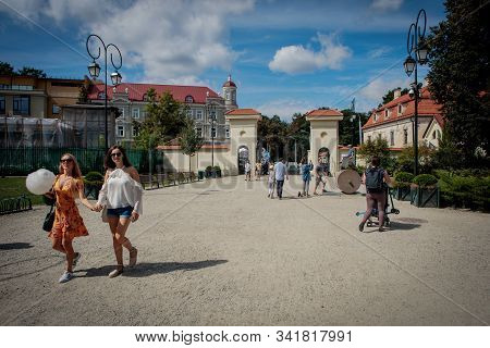 Vilnius, Lithuania - August 19, 2018: Relaxed And Happy People Stroll In Bernardinai Garden, A Publi