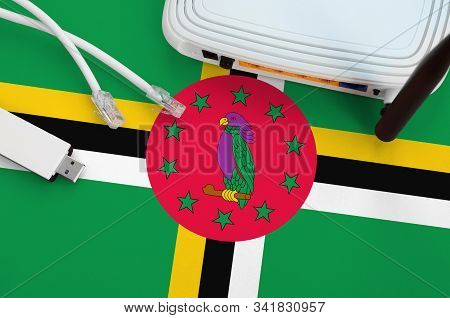 Dominica Flag Depicted On Table With Internet Rj45 Cable, Wireless Usb Wifi Adapter And Router. Inte