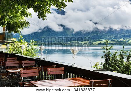 Outdoor Cafe On The Lake Wolfgangsee In Austria. Morning Mist, Rain And Clouds  Over The Austrian La