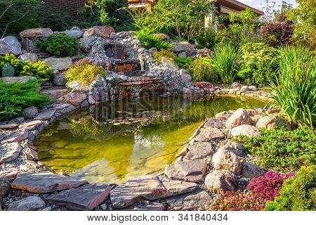 Landscape Design Of Home Garden Close-up. Beautiful Landscaping With Small Pond And Waterfall. Lands