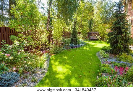Landscaping In Green Home Garden. Landscape Design With Plants And Flowers At Residential House. Sce