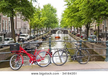 Detail of bicycles locked on top of bridge in Amsterdam, Holland, with traditional canal in the background.