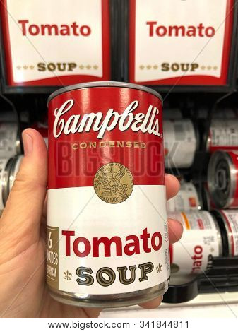 Alameda, Ca - Nov 19, 2019: Hand Holding One Can Of Campbells Brand Tomato Soup In Front Of Store Sh