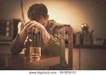 A Man With Bottle Of Whiskey On The Kitchen. The Concept Of Drunkenness And Alcoholism. Alcoholic Fa